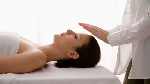Woman having a reiki massage therapy treatment