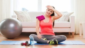 fitness, home and diet concept - smiling teenage girl with bottle of water after exercising at home